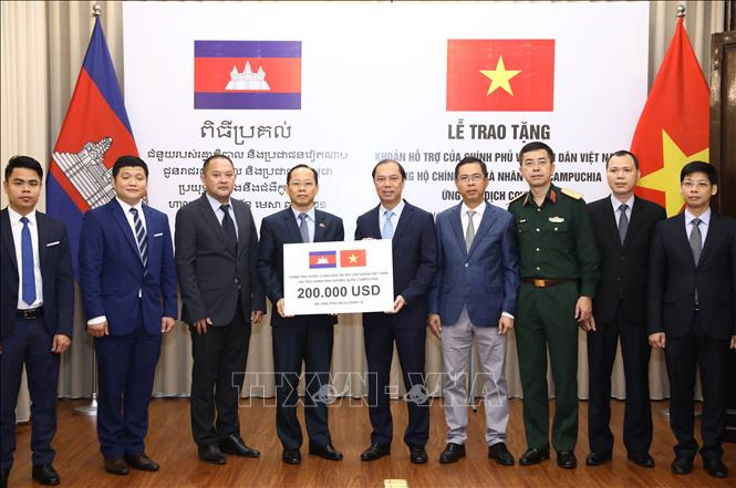 Thứ trưởng Bộ Ngoại giao Nguyễn Quốc Dũng trao tặng khoản hỗ trợ của Chính phủ và Nhân dân Việt Nam ủng hộ Chính phủ và Nhân dân Campuchia ứng phó dịch COVID-19. Ảnh: Văn Điệp/TTXVN