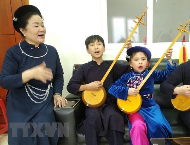 Nghệ sỹ ưu tú Hoàng Kim Tuế (trái) truyền dạy nghệ thuật hát then đàn tính cho thế hệ trẻ tỉnh Cao Bằng. (Ảnh: TTXVN phát)