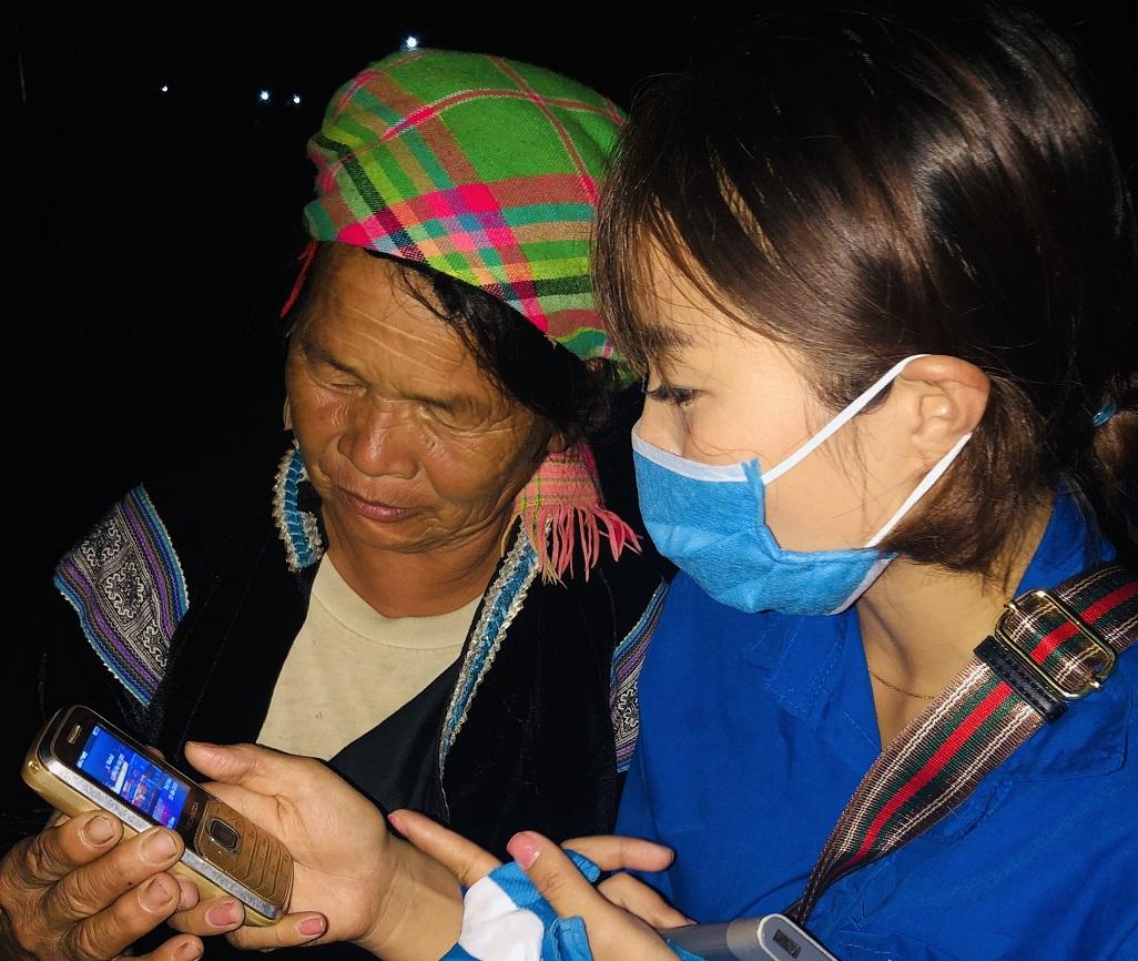 Thanh niên tình nguyện hướng dẫn một người dân tộc thiểu số ở Lai Châu cài đặt Bluezone.