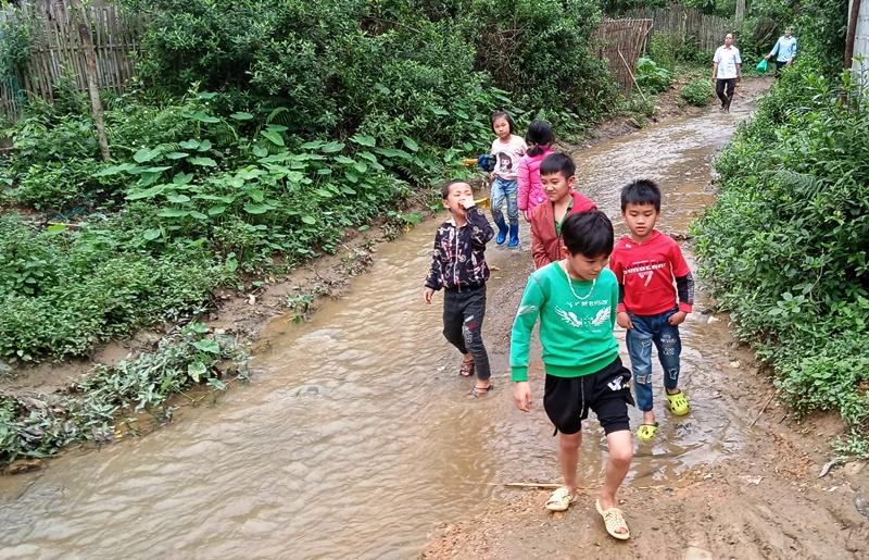 Con em xóm Tân Kim thường xuyên phải đi dọc dưới dòng suối ô nhiễm.