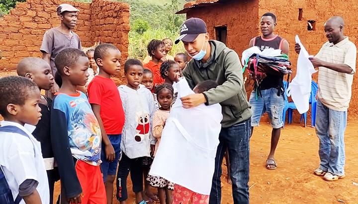 Phạm Quang Linh (ở giữa) trao đồng phục, cặp sách hỗ trợ trẻ em ở làng Sanzala (huyện Bailundo, tỉnh Huambo, Angola) đến trường học. (Nguồn: Nhân dân)