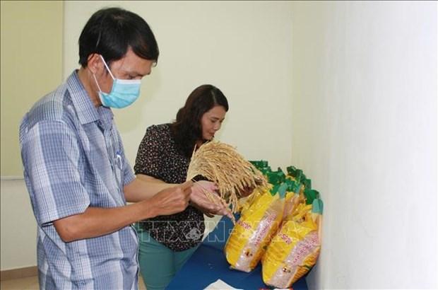 Khách hàng tìm hiểu thông tin sản phẩm gạo Mắt rồng. Ảnh: Xuân Anh - TTXVN