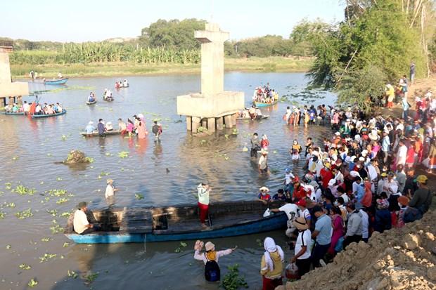 Người dân đi đò qua sông Lũy để đến khu nghĩa trang của người Chăm. Ảnh: Nguyễn Thanh - TTXVN
