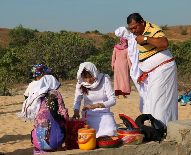 Chuẩn bị đồ cúng và mặc đồ truyền thống để thực hiện Lễ tảo mộ. Ảnh: Nguyễn Thanh - TTXVN