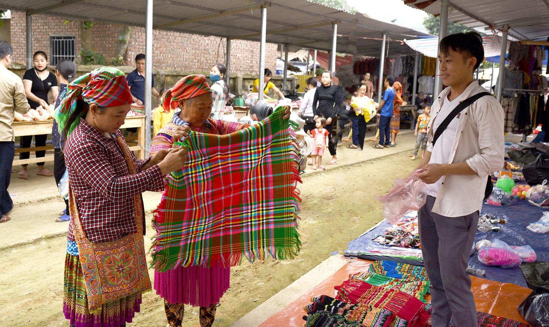 Hai người Mông đang trả giá một chiếc khăn thổ cẩm, đây là chiếc khăn mà người phụ nữ Mông thường đội đầu.