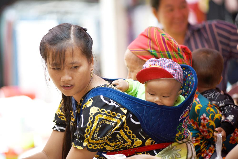 Các em bé cũng theo mẹ xuống chợ bằng những chiếc địu.