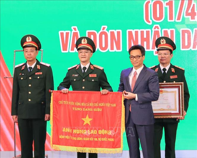 Thay mặt lãnh đạo Đảng, Nhà nước, Phó Thủ tướng Vũ Đức Đam trao Danh hiệu Anh hùng Lao động thời kỳ đổi mới cho Bệnh viện Trung ương Quân đội 108. Ảnh: TTXVN