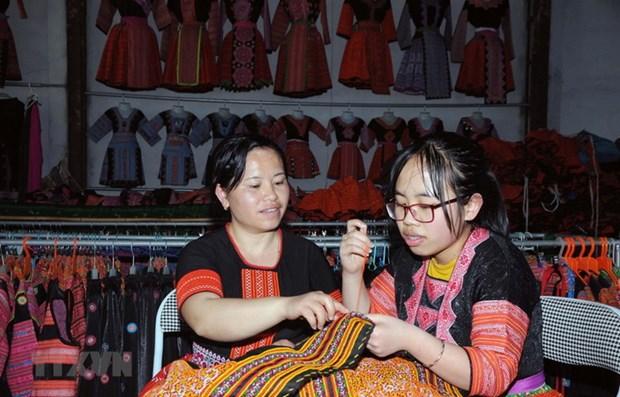 Chị Tráng Thị Dua (bên trái) truyền dạy nghề thêu, may truyền thống của đồng bào dân tộc Mông cho con gái. (Ảnh: Quang Quyết/TTXVN)
