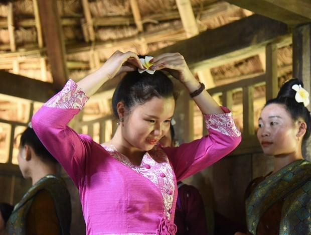 Thiếu nữ dân tộc Lào sửa soạn trang phục chuẩn bị cho nghi lễ. Ảnh: Diễm Quỳnh