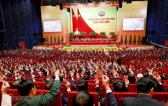 Các đại biểu biểu quyết, thông qua Nghị quyết Đại hội XIII Đảng Cộng sản Việt Nam. (Ảnh: TTXVN).
