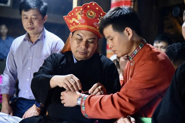 Thầy mo buộc sợi chỉ đỏ may mắn cho mọi người trong buổi lễ. Ảnh: Diễm Quỳnh