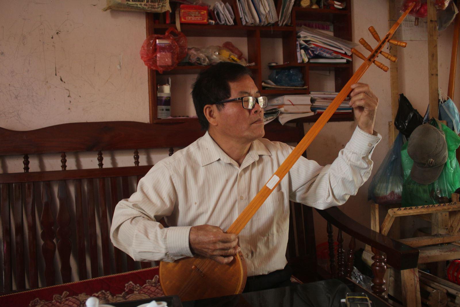 Ông Đàm Xuân Hòa say sưa với cây đàn tính 6 dây của mình.