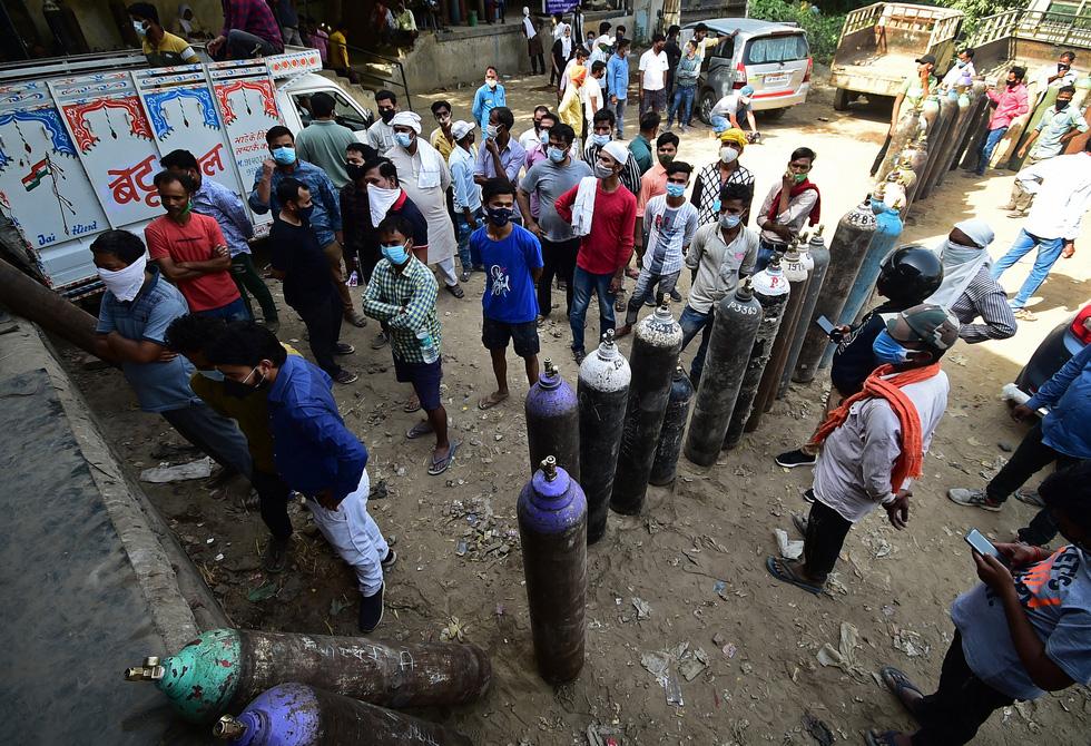 Người dân đợi bơm đầy các bình oxy y tế dành cho bệnh nhân COVID-19 tại một trạm bơm oxy ở thành phố Allahabad, bang Uttar Pradesh, miền bắc Ấn Độ hôm 24-4. (Ảnh theo Reuters.com)