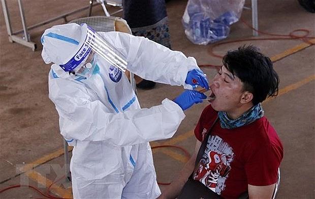 Bác sỹ đang lấy mẫu xét nghiệm cho một người dân Vientiane tại một điểm xét nghiệm dã chiến. (Nguồn: TTXVN)
