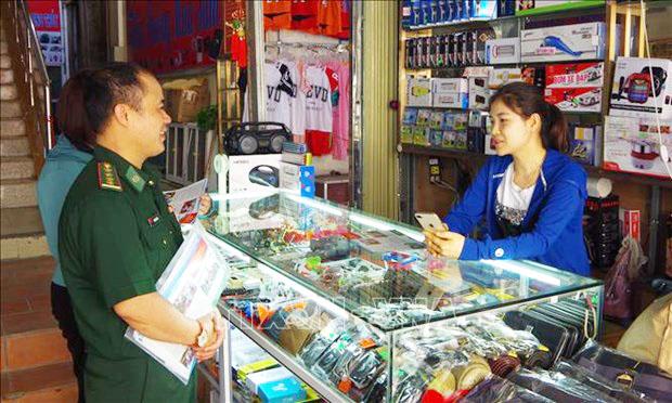 Cán bộ biên phòng tỉnh Lạng Sơn tuyên truyền bầu cử đến các tiểu thương kinh doanh tại chợ Tân Thanh (Lạng Sơn) Ảnh: Quang Duy - TTXVN