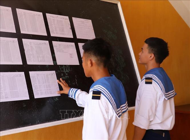 Hai chiến sỹ trẻ lần đầu tiên được đi bầu, theo dõi danh sách cử tri được niêm yết tại UBND xã Song Tử Tây (huyện Trường Sa, tỉnh Khánh Hoà).