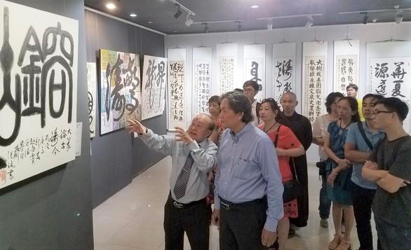 Họa sư Trương Lộ (trái) giới thiệu với công chúng tại triển lãm thư pháp của mình