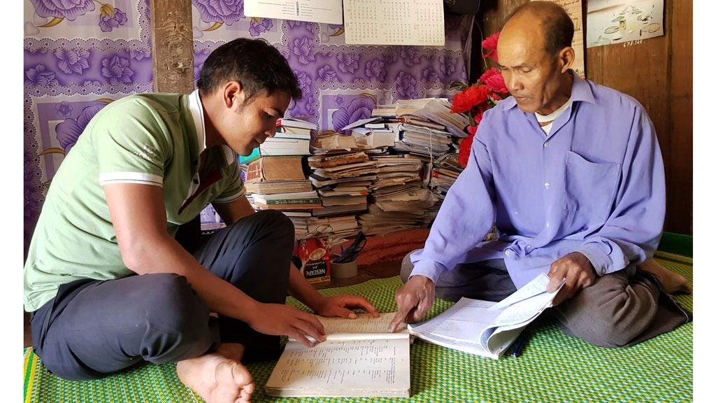 Già làng, thầy giáo Ya Loan (phải) hướng dẫn ngôn ngữ Chu Ru cho cán bộ xã (Ảnh TL)
