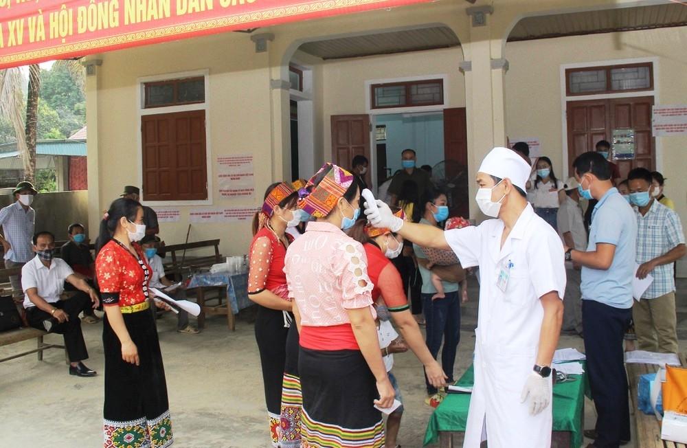 Cử tri ở Con Cuông, Nghệ An được kiểm tra thân nhiệt và sát khuẩn tay trước khi vào khu vực bỏ phiếu