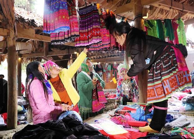 Những phụ nữ Mông bên gian hàng trang phục truyền thống tại chợ phiên Sin Suối Hồ, huyện Phong Thổ (Lai Châu). Ảnh: Nguyễn Oanh - TTXVN