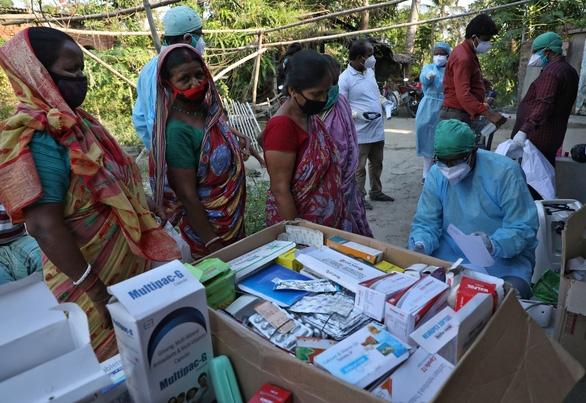 Người dân tại làng Debipur, bang Tây Bengal, Ấn Độ, nhận thuốc từ nhân viên y tế ngày 21/5 trong đại dịch COVID-19. Ảnh: Reuters
