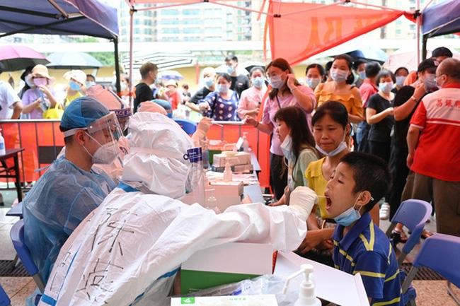 Chuyên gia y tế lấy mẫu xét nghiệm một trẻ nhỏ tại một sân vận động ở Quảng Châu ngày 30/5. Ảnh: Reuters