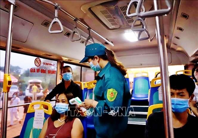 Hành khách đi xe buýt đảm bảo giãn cách và được đo thân nhiệt. Ảnh: TTXVN