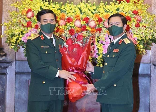 Thượng tướng Phan Văn Giang, Ủy viên Bộ Chính trị, Bộ trưởng Bộ Quốc phòng tặng hoa chúc mừng Thượng tướng Nguyễn Tân Cương. Ảnh: Thống Nhất/TTXVN