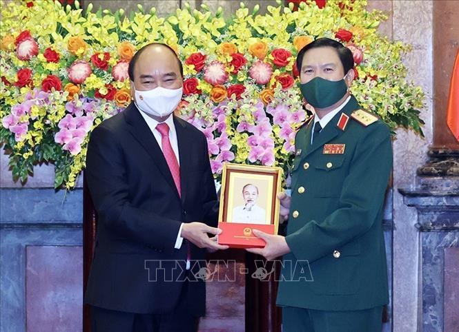 Chủ tịch nước Nguyễn Xuân Phúc tặng chân dung Chủ tịch Hồ Chí Minh cho Thượng tướng Nguyễn Tân Cương. Ảnh: Thống Nhất/TTXVN