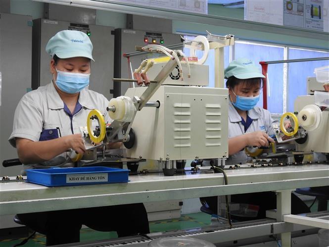 Công nhân Công ty TNHH Tabuchi Electric Việt Nam, KCN Đại Đồng - Hoàn Sơn (Bắc Ninh) đeo khẩu trang, ngồi giãn cách, đảm bảo duy trì hoạt động sản xuất. Ảnh: Thái Hùng/TTXVN