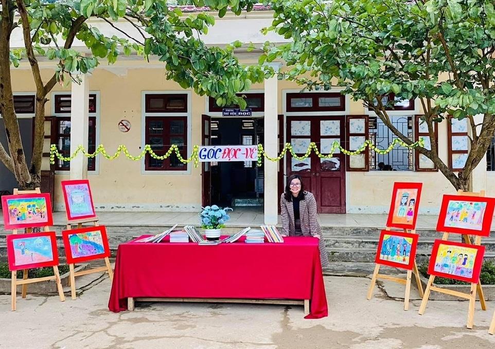 """Cô Lã Thị Thanh Huyền tại góc đọc - vẽ trong """"Phiên chợ vùng cao"""" của Trường TPCS dân tộc bán trú Tây Sơn"""