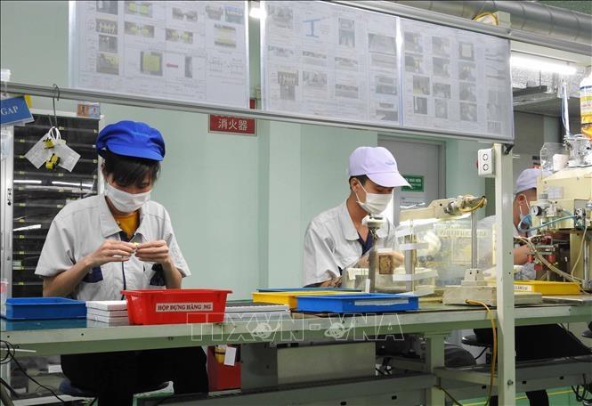Đảm bảo an toàn COVID-19 tại các nhà máy sản xuất. Ảnh: TTXVN.