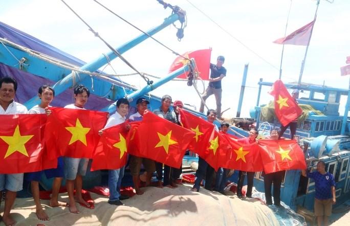 Những lá cờ đầu tiên đã đến tận tay ngư dân tỉnh Bình Thuận. (Nguồn: Báo Người Lao động)