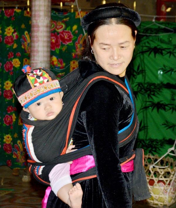Người mẹ Tày địu em bé trên lưng (Ảnh: Báo Tuyên Quang)