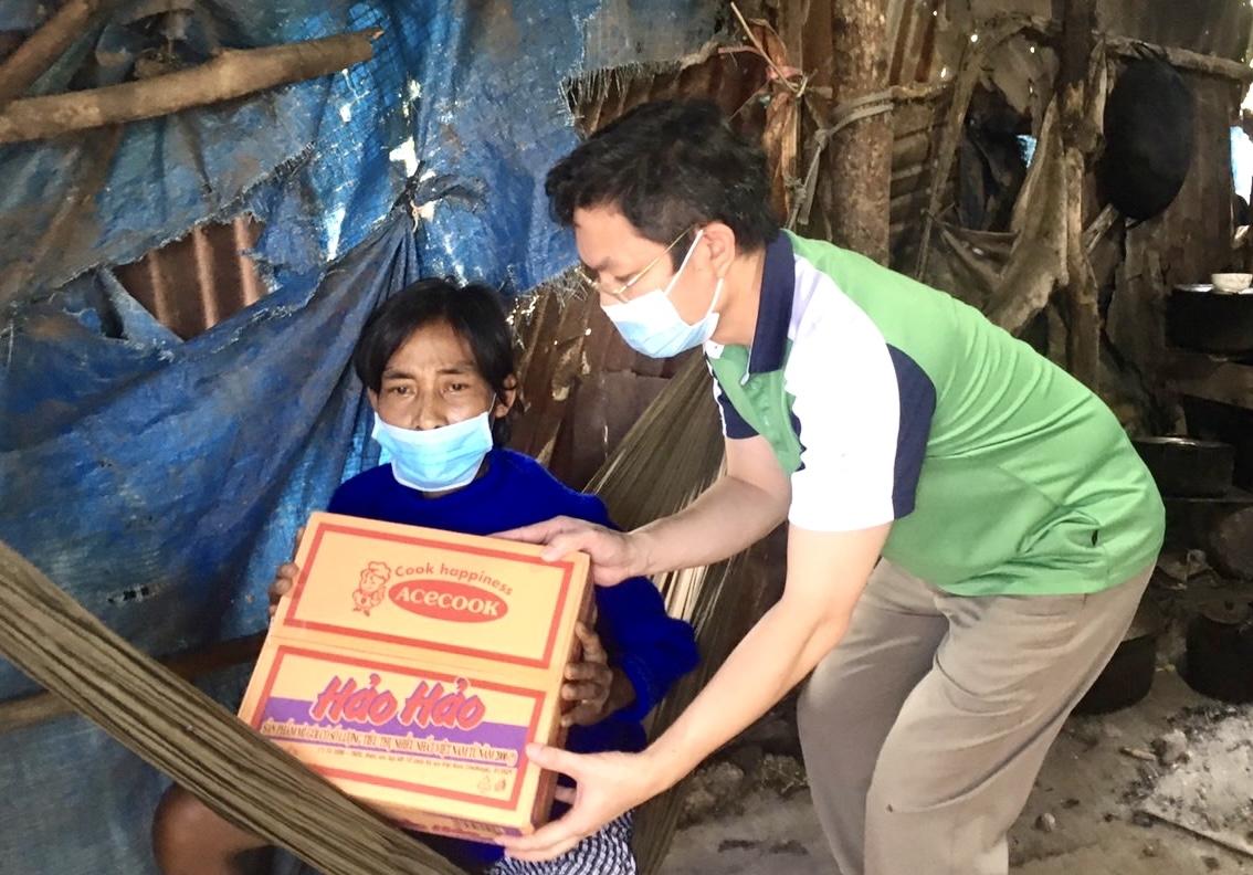 Nhà báo Lê Thuận, Phóng viên Báo Dân tộc và Phát triển trao quà của bạn đọc cho Phạm Văn Hậu, con trai bà Nguyễn Thị nghẹ