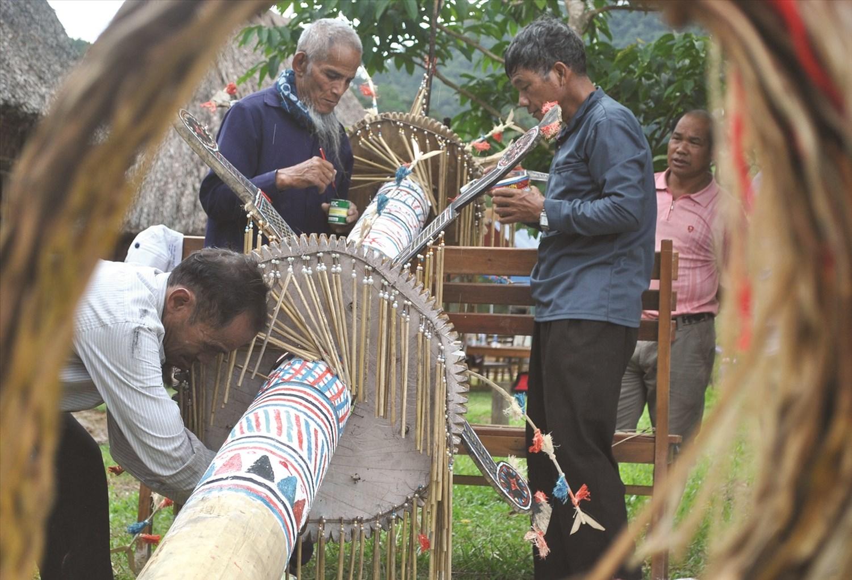 Già Trần Văn Trân (mặc áo xanh đậm đứng chính giữa), cùng các nghệ nhân trong thôn 1 trang trí cho cây nêu.