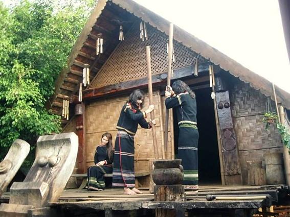 Phụ nữ Ê Đê giã gạo bên đầu hồi nhà dài truyền thống