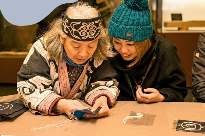 Người Ainu (bên trái) giới thiệu về nghề thêu thủ công truyền thống tại Bảo tàng Akanko Ainu Kotan