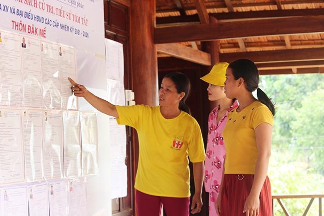 Chị Khiêm (bên trái) hướng dẫn người dân tìm hiểu về công tác bầu cử tại nhà Rông thôn Đắk Mế