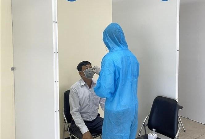 Nhân viên y tế thực hiện lấy mẫu cho hành khách theo quy trình thực hiện test nhanh kháng nguyên COVID-19 ở Cảng hàng không Quốc tế Cam Ranh. Ảnh: Phan Sáu/ TTXVN