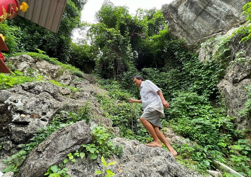Hàng ngày, người quản lý khu di tích là ông Bùi Văn Nhàng mặc dù chân đau nhưng vẫn chống gậy lên chăm nom khu đền thượng. (Ảnh: Xuân Mai/Vietnam+)