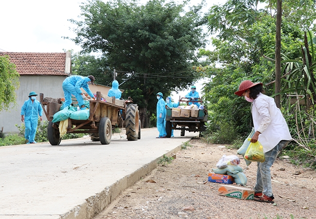 Lực lượng chức năng xã Ea Trol vận chuyển nhu yếu phẩm bằng xe máy cày hỗ trợ người dân đang bị phong tỏa ở buôn Ly, xã Ea Trol