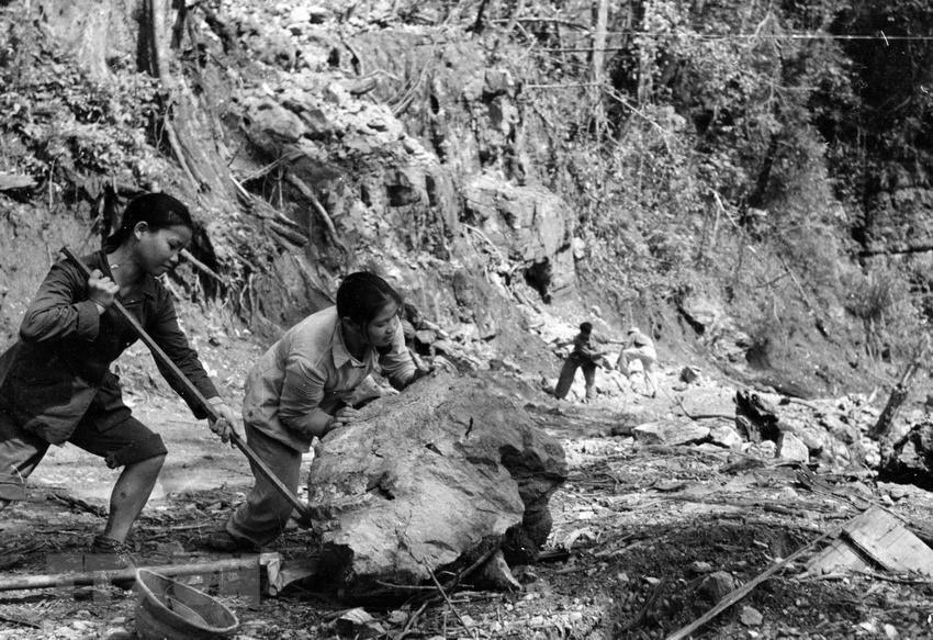 Thanh niên xung phong đẩy đá, mở đường cho xe qua trên tuyến đường Trường Sơn. (Ảnh: Hữu Ngôi/TTXVN)