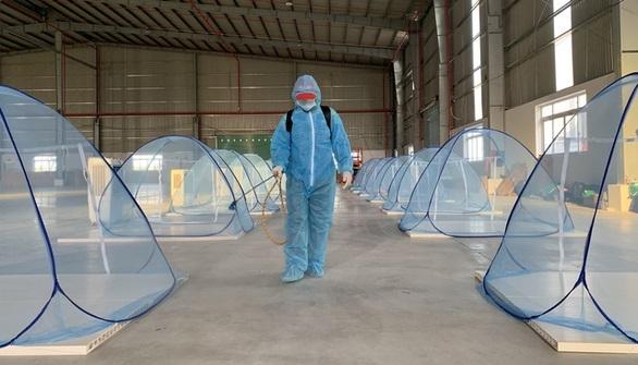 Nhân viên Tập đoàn Đại Việt phun hóa chất khử khuẩn khu lưu trú tập trung của công nhân, đảm bảo an toàn cho công nhân vừa cách ly vừa sản xuất - Ảnh: Hiệp Trần
