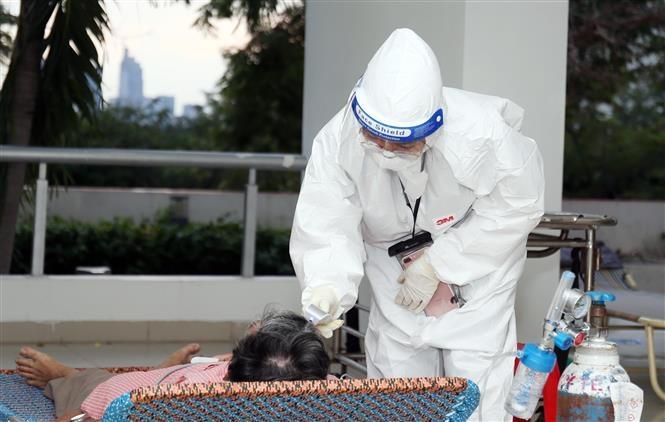 Y bác sĩ luôn phải mặc bảo hộ kín mít tránh lây nhiễm. Ảnh: TTXVN