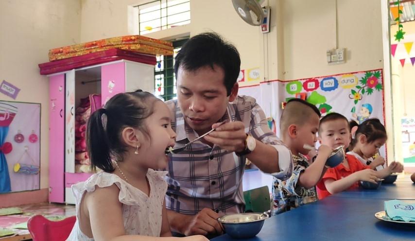 Thầy giáo Trịnh Hồng Quân – Hiệu trưởng Trường Mầm non Thành Sơn (Bá Thước, Thanh Hóa) đang cho trẻ ăn trưa tại trường.