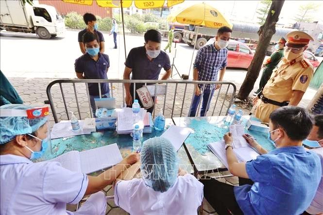 Lực lượng chức năng làm nhiệm vụ kiểm soát dịch bệnh tại chốt Quốc lộ 5 đoạn trên địa bàn huyện Gia Lâm (TP Hà Nội). Ảnh: TTXVN
