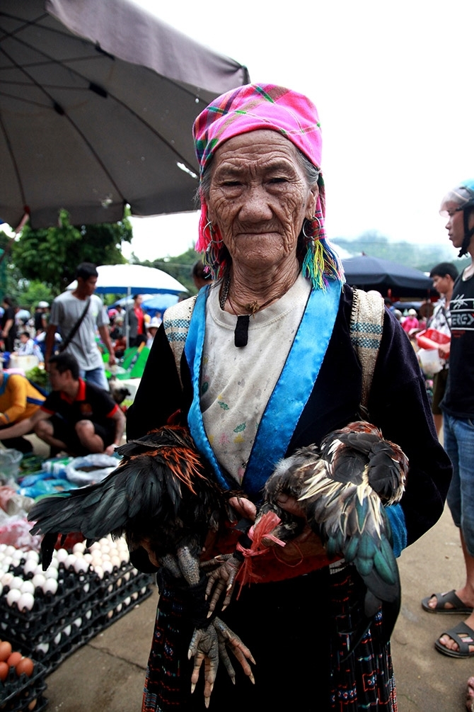 Người phụ nữ dân tộc Mông mang 2 con gà xuống chợ phiên để bán