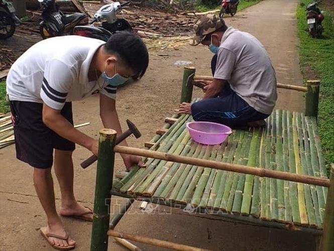 Bà con đồng bào thiểu số S'tiêng ở ấp Sóc Răng, xã Thanh Bình (Hớn Quản, Bình Phước) làm giường tặng khu cách ly. Ảnh: TTXVN