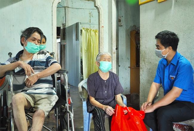 Bí thư Tỉnh Đoàn Trần Quốc Duy (bìa phải) ân cần hỏi thăm sức khỏe mẹ liệt sĩ Phạm Thị Yếng và gia đình của mẹ